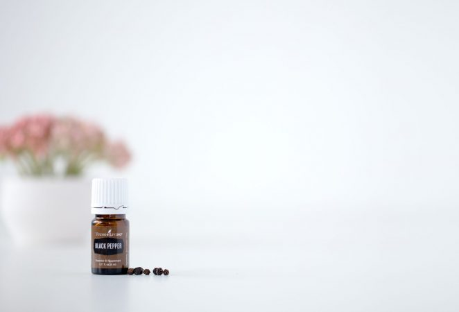 a bottle of black pepper essential oil on a white background with a few peppercorns and a bouquet faded in the background